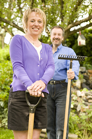 A couple stands with a shovel